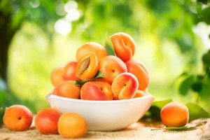 Apricot. Ripe Organic Apricots with leaves on a white wooden tab