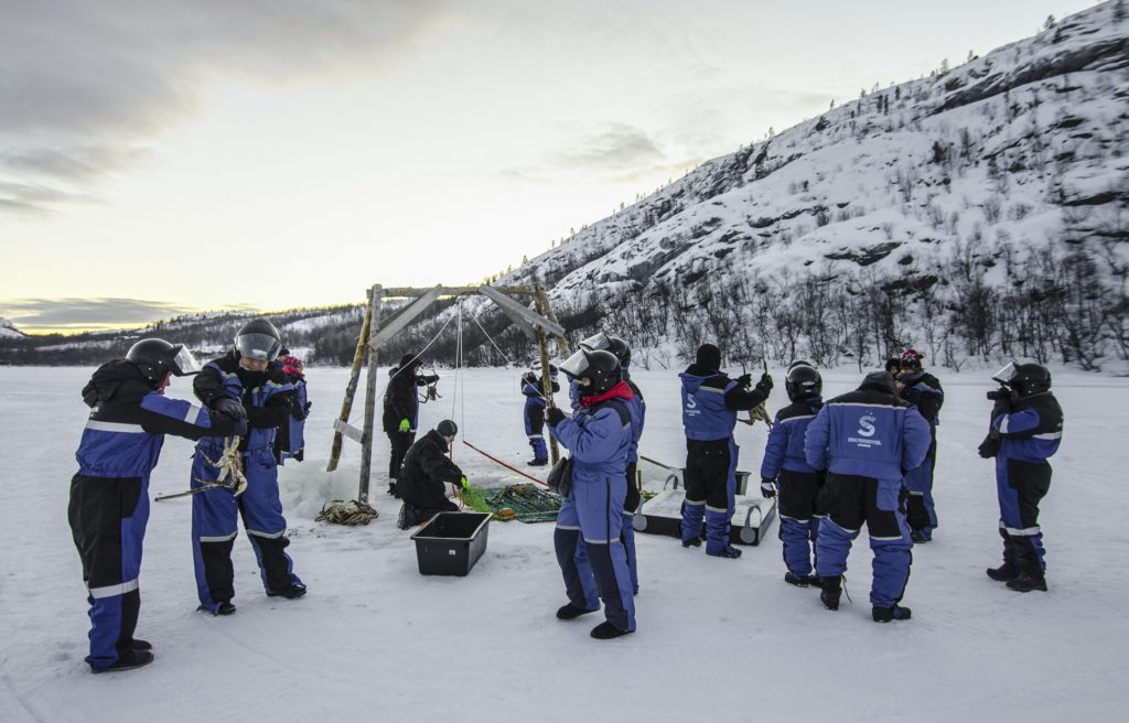 Guests King Crab ice fishing in their Norway Arctic Suits